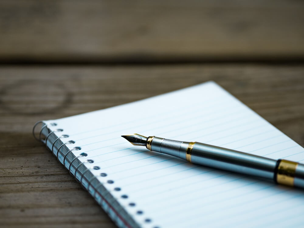 Picture of a pen resting on a notebook.